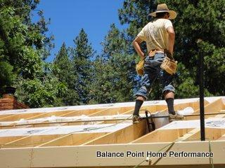 Man standing on an unfinished roof wearing tool belt